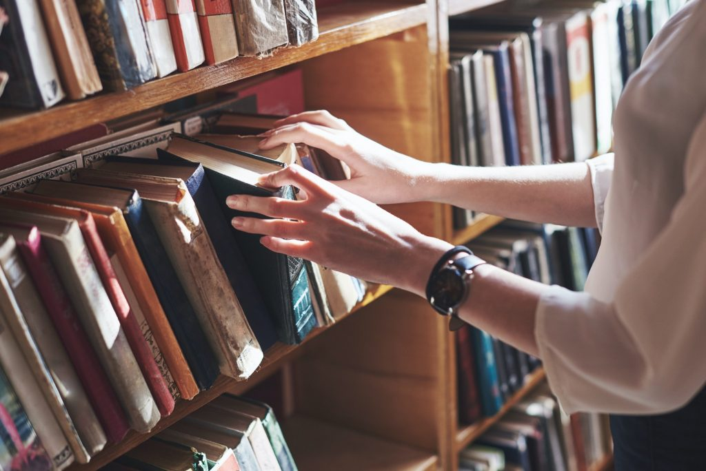 A young girl student looking for literature near the bookshelves in the old library